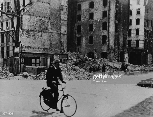 A cyclist riding through the ruins of Rotterdam Holland soon after the invasion of 1940