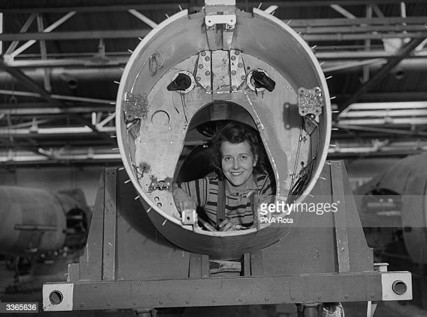 A female factory worker solders small parts in the tail section of a Mosquito bomber the fastest aircraft in operation in the world