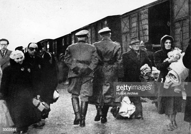 Nazi officers supervise Jews leaving railway trucks during the deportation to the camps