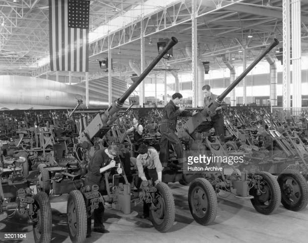 A fulllength view of young male workers wearing uniforms assembling 40 millimeter antiaircraft guns in a factory where a US flag hangs from the...