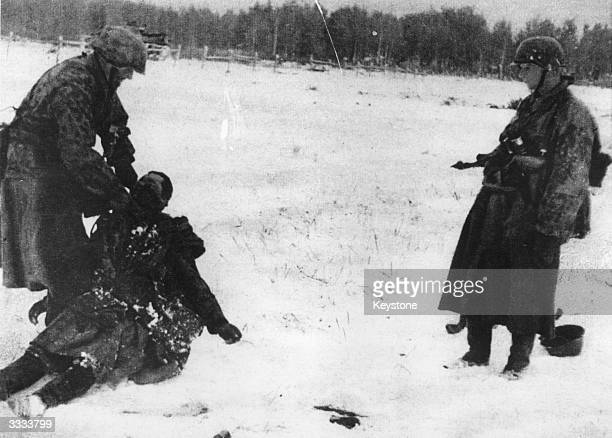 A German soldier prevents a comrade from falling asleep in a snowcovered Russian field as it would mean certain death in these conditions