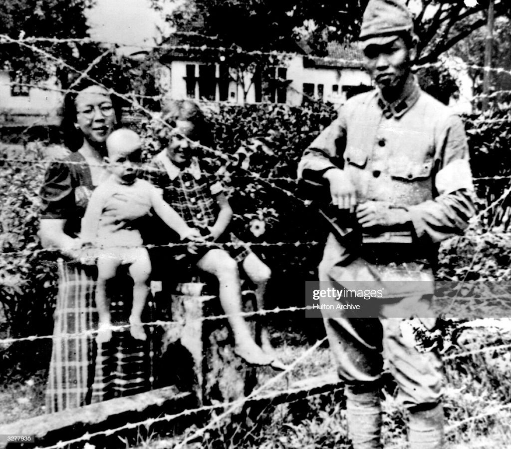 A Japanese soldier poses in front of a barbed wire fence behind which are women and children