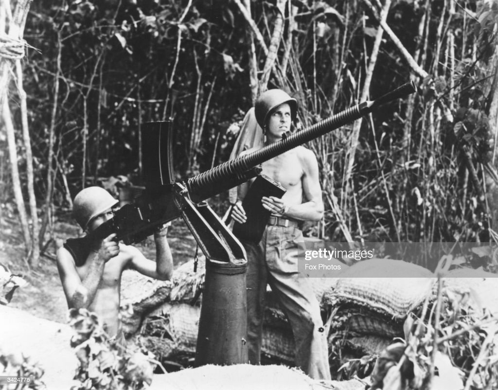 A machine gun captured from the Japanese at Guadalcanal is being used by two American marines