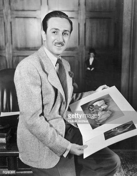 A portrait of American cartoonist and producer Walt Disney seated on the edge of a desk in an office holding illustrations from his animated films...