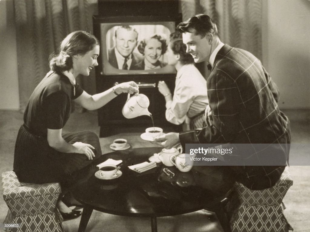A young woman smiles and pours tea for a man as they sit in a living room watching American comedy duo George Burns and Gracie Allen on the...