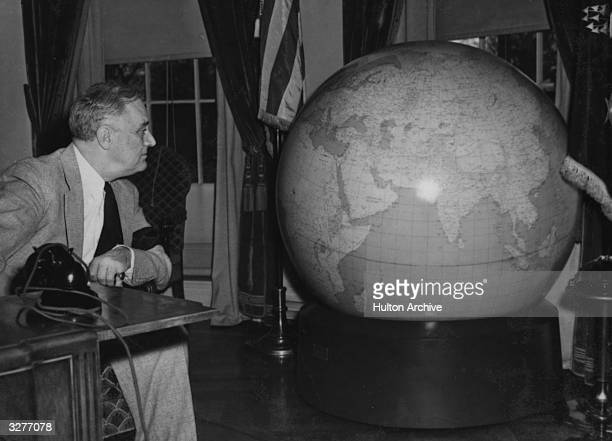 American President Franklin Delano Roosevelt inspecting a Christmas present from the army a huge globe showing the areas where American troops were...