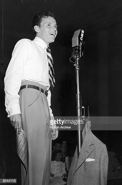 American singer and actor Frank Sinatra stands and smiles behind a microphone holding sheet music during an NBC radio broadcast of his performance...