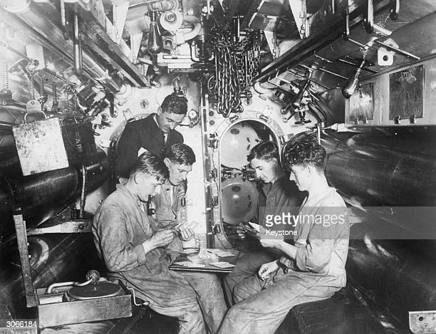 Crew of a submarine docked in Portsmouth having a game of cards while listening to a gramophone record in the torpedo firing room
