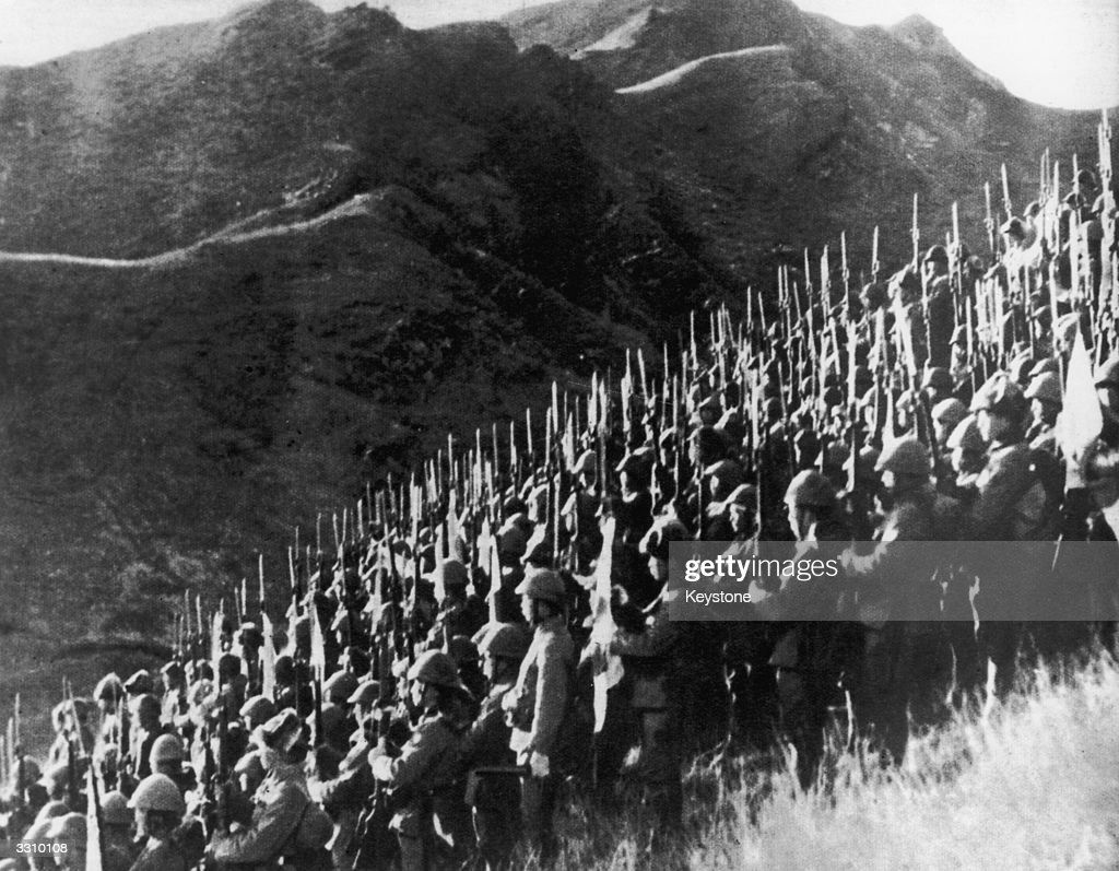 Japanese troops present arms to the 'Rising Sun' as they amass on the Indochina Burmese border