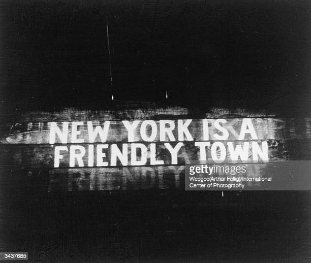 **NOT TO BE USED FOR POSTCARDS** At nighttime an illuminated sign reads 'New York is a Friendly Town' Photo by Weegee/International Center of...