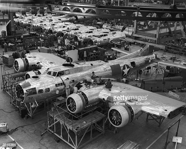 People working on a B17 Flying Fortress plane and plane parts under construction at the Lockheed plant in Burbank California World War II