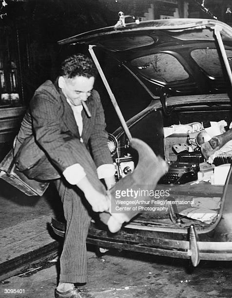 Polishborn American photographer Arthur 'Weegee' Fellig pulls on his Wellington boots at the back of his car which contains a typewriter and a jumble...