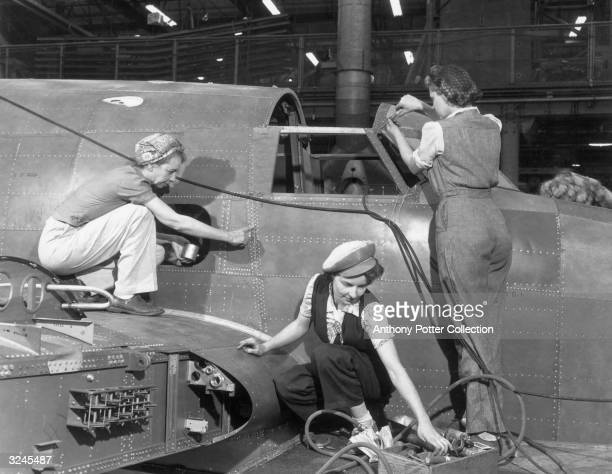 Three female workers assemble the fuselage of an airplane at the Lockheed Aircraft Corporation Plant Burbank California