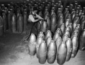 A factory worker moves large cylindrical bombs in a warehouse during World War II