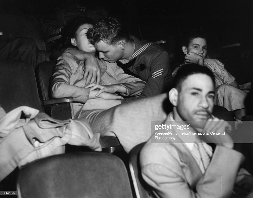 A sailor fondling a girl at the movie theatre. Taken with infrared negative. (Photo by Weegee(Arthur Fellig)/International Center of Photography/Getty Images)