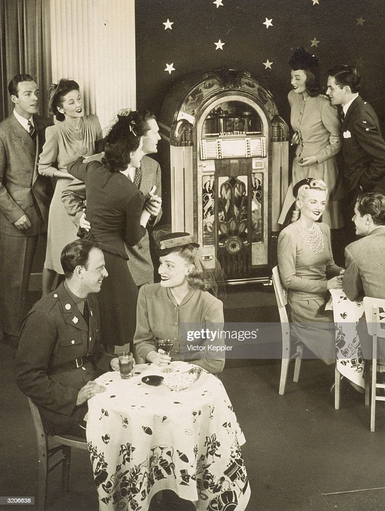 Advertisement shows a group of servicemen in uniform and their female companions sitting at tables and dancing around a Wurlitzer jukebox, 1940s.