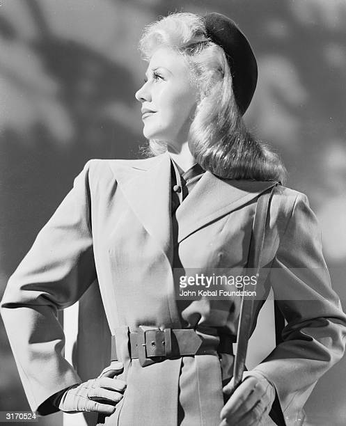 American dancer and actress Ginger Rogers wearing a belted raincoat and a beret