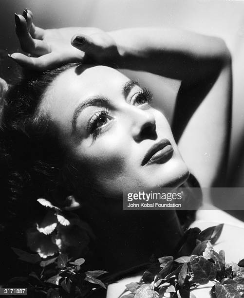 American film actress Joan Crawford with her hand on her brow