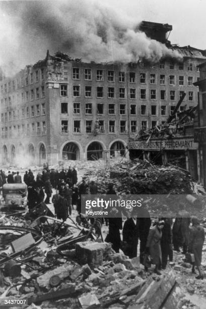 Citizens of Hamburg going about their business in the streets of Hamburg surrounded by bomb sites and a wrecked building with smoke stiil pouring...