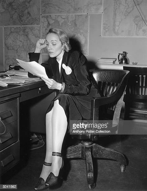 Germanborn actor Marlene Dietrich wearing a skirt suit sits at a desk reviewing paperwork related to her war efforts World War II Maps of Africa...