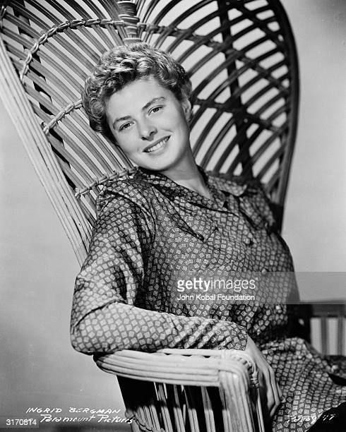 Sitting in a highbacked wicker chair film star Ingrid Bergman wearing a matronly print top with long sleeves and sporting a short hairstyle for her...