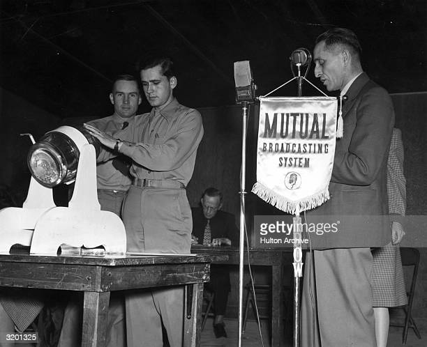 Two US soldiers draw numbers from a tumbler as a radio announcer reads the results into a microphone for a lottery drawing for the US draft in World...
