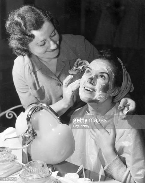 A smiling beautician applies a facial cream on the face of a young woman who looks up and presses plastic gown towards her chest