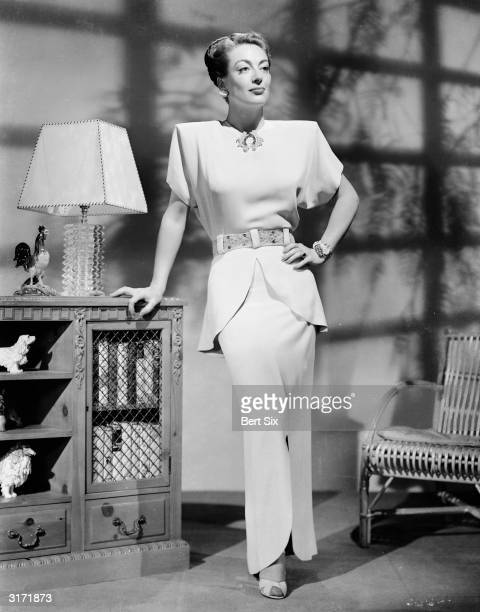 American film actress Joan Crawford leaning on a sideboard