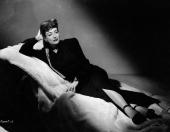 American film actress Joan Crawford reclining on a rug covered sofa