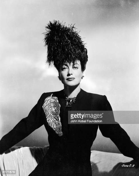American film actress Joan Crawford wearing a hat decorated with feathers and a suit with a large leaf design brooch