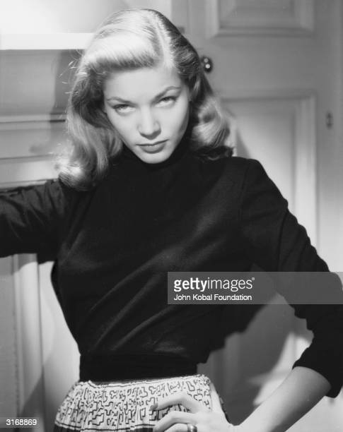American screen star Lauren Bacall lowers her head and gazes up from under her brows with her famously sultry expression