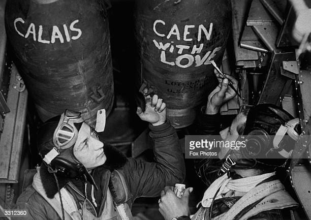 An air crew paint slogans on the bombs they are about to deliver to the enemy