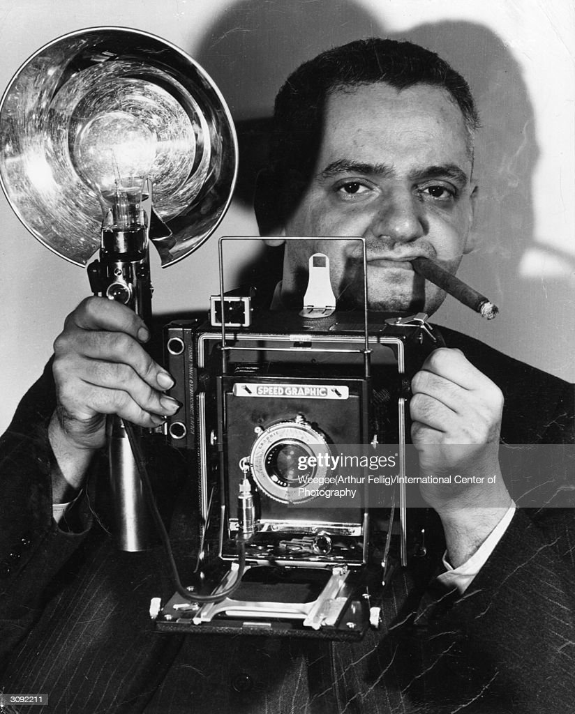 Polish-born American photographer Arthur Fellig (1899 - 1969) with his Speed Graphic camera. He was known by the police as 'Weegee' for his ouija-like prescience of crime scenes and disasters. In fact he kept a radio in his car tuned to the police frequency, and was often able to reach the scene before the police themselves. (Photo by Weegee(Arthur Fellig)/International Center of Photography/Getty Images)