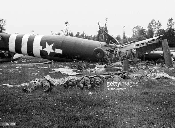 The bodies of eight dead American members of an airborne division lie beside the wreckage of the Horsa glider which delivered them to Normandy