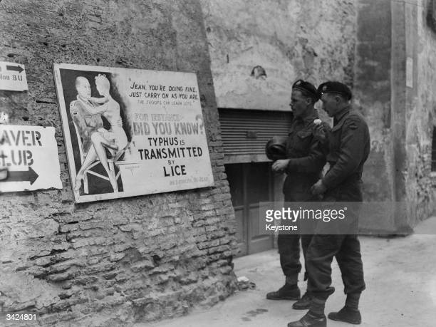 Two Canadian soldiers looking at a warning about lice carrying typhus on a wall in Italy