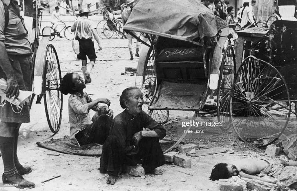 Victims of a Japanese bombing raid over Singapore sit suffering in the street next to a rickshaw.