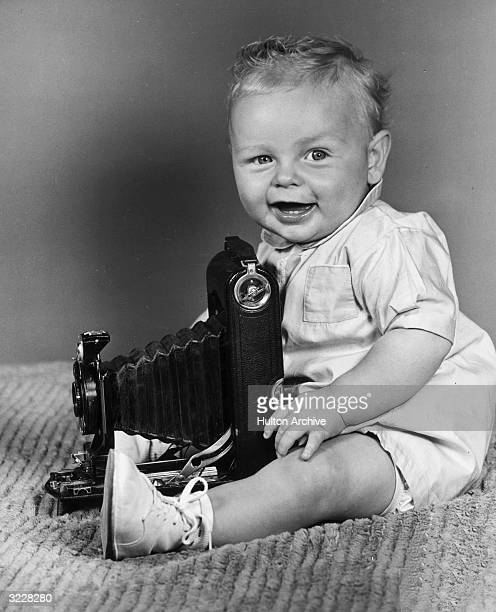 A baby laughs while sitting on a blanket behind a Kodak camera 1940s