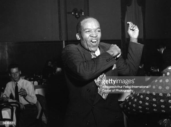 A black American man snapping his fingers to the music Photo by Weegee/International Center of Photography/Getty Images