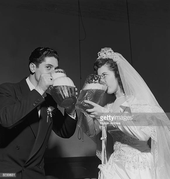 A bride and groom drink out of separate pitchers of beer