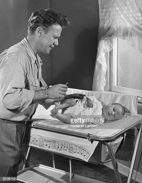 A father holds a safety pin as he attempts to change his baby's diaper 1940s The baby lays on top of a changing table