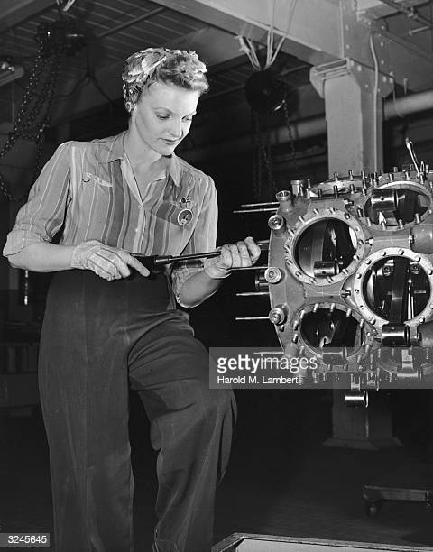 A female factory worker wearing trousers with her hair tucked into a scarf uses a screwdriver to work on a part in a manufacturing plant 1940s