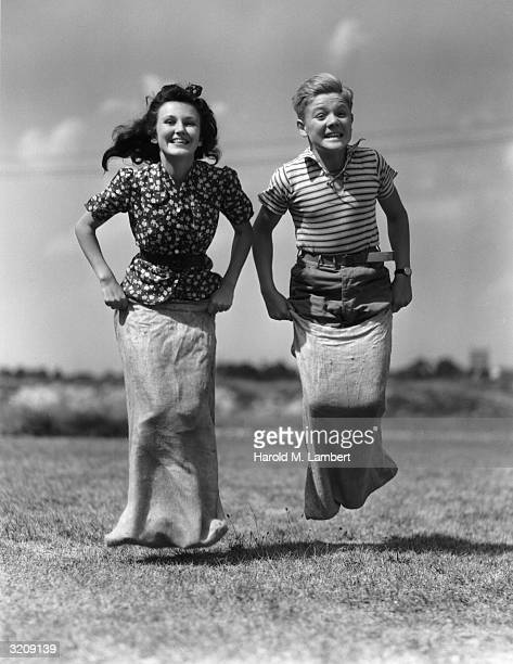 A girl and a boy jumping in a potato sack race