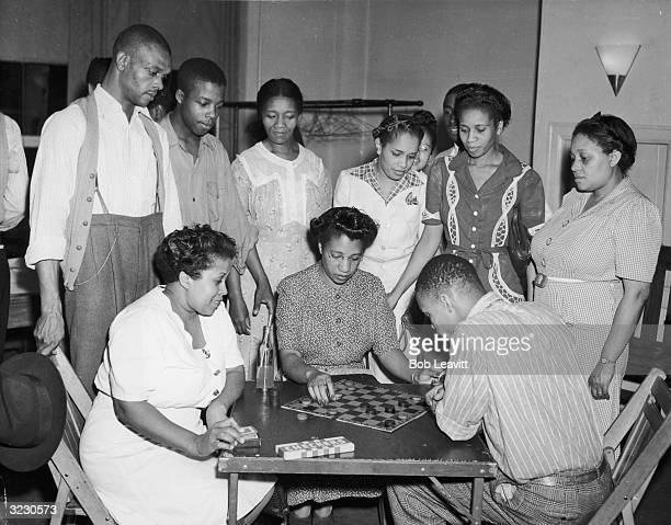 A group of AfricanAmerican men and women watch as a young man and woman play a game of checkers at a card table Another woman sits at the table...