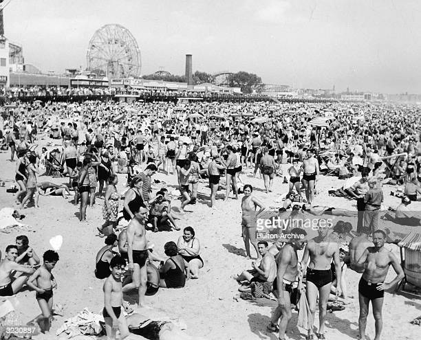 A huge crowd of people in swimsuits on the beach at Coney Island with the ferris wheel and Cyclone rides visible in the background Brooklyn New York...