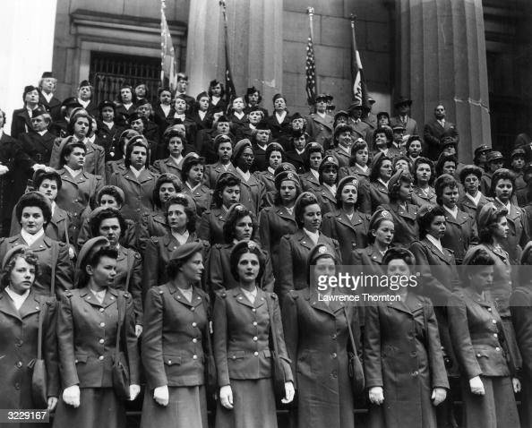A large group of U S military cadet nurses stand in rows wearing their uniforms outside the recruitment center on Broad and Wall Streets New York City