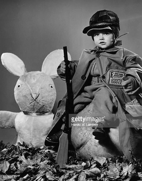 A little boy in a hunting outfit and holding a toy rifle poses on a pumpkin next to a large stuffed rabbit