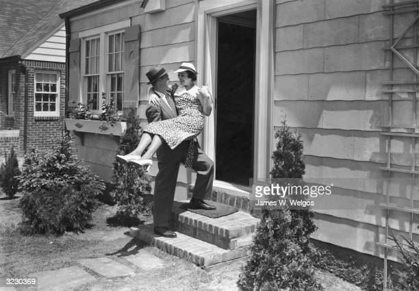 A man carries his new bride in his arms over the threshold of their house She wears a floral print dress with a hat and high heels