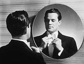 A man in a formal jacket faces a round wall mirror and adjusts his bow tie