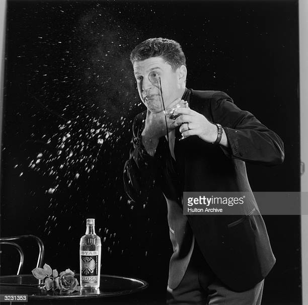A man wearing as monocle clutches his throat and spits a martini out of his mouth A bottle of Vodka and a red rose sit on a table next to him