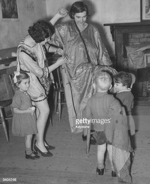 A mother dresses up for the Christmas pantomime as her children watch